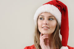 Cute young woman in Santa hat dreaming about Christmas gifts Stock Image