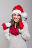 Cute young woman with Santa hat enjoying coffee Stock Image