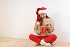 Cute young woman in santa hat with present box in hands Stock Images