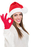 Cute young woman with Santa hat showing ok gesture Royalty Free Stock Photos