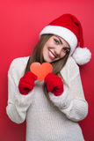 Cute young woman with Santa hat showing red paper heart Stock Image