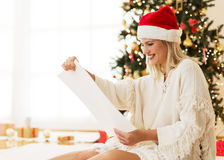 Cute, young woman with Santa's hat reading from a list Royalty Free Stock Photos