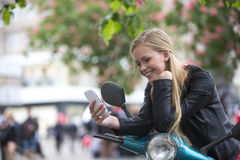 Cute young woman on a scooter laughing looking at the phone royalty free stock photography