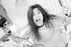 Cute young woman screaming for messy hair trying to dry and brush closeup. Unhappy woman with long hair problem with knot Royalty Free Stock Photos