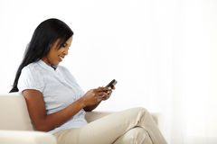 Cute young woman sending a text message Royalty Free Stock Image