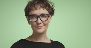 Cute young woman with short hair on colorful backgrounds. Pretty joyful smiling young woman with dark short hair wearing a black top and glasses isolated on royalty free stock photo