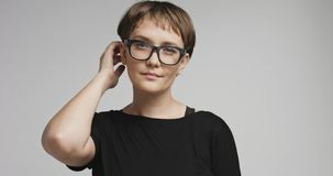 Cute young woman with short hair on colorful backgrounds. Pretty joyful smiling young woman with dark short hair wearing a black top and glasses isolated on stock photography