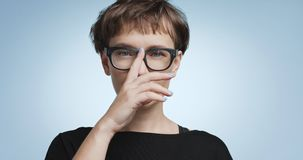 Cute young woman with short hair on colorful backgrounds. Pretty joyful smiling young woman with dark short hair wearing a black top and glasses isolated on stock images
