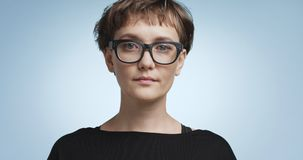 Cute young woman with short hair on colorful backgrounds. Pretty joyful smiling young woman with dark short hair wearing a black top and glasses isolated on royalty free stock images