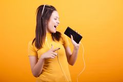 Cute young woman singing on her phone and pointing royalty free stock image