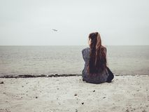 Cute young woman sits on the sand on the beach and looks out into the distance royalty free stock photo