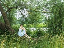Cute young woman sitting on a beautiful, flowering tree Stock Image