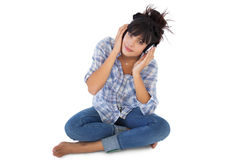 Cute young woman sitting on the floor listening to music Stock Image