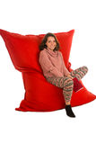 Cute young woman sitting on red beanbag sofa chair for living ro Stock Image