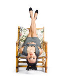 Cute young woman sitting upside down on chair Royalty Free Stock Image