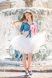 Cute young woman in a skirt near the fountain Royalty Free Stock Photo