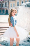 Cute young woman in a skirt near the fountain Royalty Free Stock Photos