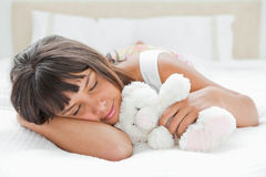 Cute young woman sleeping with a teddy bear Royalty Free Stock Photo