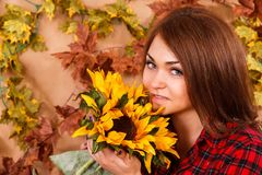 Cute young woman smelling the sunflowers Stock Photography