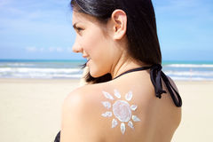 Cute young woman smiling on the beach in bikini with sun painted with cream on the back Royalty Free Stock Photos