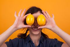 Cute young woman smiling at the camera with oranges as eyes over yellow background in studio. Juicy oranges. Tasty oranges. Lady with tasty oranges stock photo