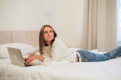 A cute young woman smiling excitedly at her laptop screen. She is relaxing in bed. A cute young woman smiling excitedly at her laptop screen. She is relaxing in royalty free stock image