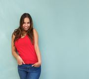 Cute young woman smiling with hands in pocket Royalty Free Stock Image