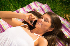 Cute young woman speaking on a mobile phone on the grass Royalty Free Stock Images