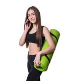 Cute young woman in sportswear with green mat ready for workout. Smiling and talking on the phone. Isolated on white background. Royalty Free Stock Photo