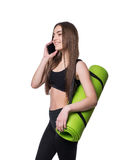 Cute young woman in sportswear with green mat ready for workout. Smiling and talking on the phone. Isolated on white background. Stock Photo