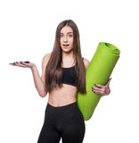 Cute young woman in sportswear with green mat ready for workout. Smiling and talking on the phone. Isolated on white background. Cute young woman in sportswear Royalty Free Stock Photos