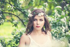 Cute young woman on spring flowers and green leaves background. Pretty model girl face, outdoor portrait royalty free stock photo