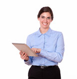 Cute young woman standing working on tablet pc Stock Image