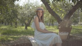Cute young woman in straw hat and long white dress looking at the camera smiling sitting in the green summer garden. Rural lifestyle stock video footage