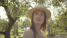 Cute young woman in straw hat and long white dress looking at the camera smiling standing in the green summer garden. An attractive young woman in a straw hat stock video