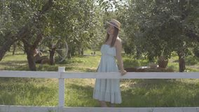 Cute young woman in straw hat and long white dress looking at the camera smiling standing in the green summer garden. Attractive young woman in a straw hat and stock video