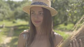 Cute young woman in straw hat and long white dress looking at the camera smiling standing in the green summer garden. Attractive young woman in a straw hat and stock footage