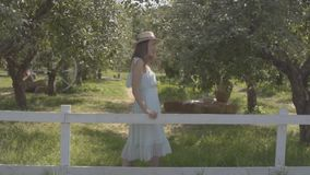 Cute young woman in straw hat and long white dress looking at the camera smiling standing in the green summer garden. Behind the fence. Rural lifestyle. Slow stock footage