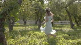 Cute young woman in straw hat and long white dress running through the green summer garden. Carefree rural life. Connection with nature stock video footage
