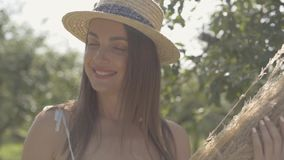 Cute young woman in straw hat and long white dress standing in the green summer garden holding bunch of dry grass. Rural. Lifestyle. Slow motion stock video footage