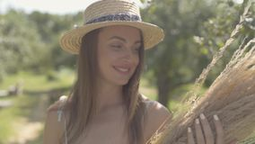 Cute young woman in straw hat and long white dress standing in the green summer garden holding bunch of dry grass. Rural. Lifestyle. Slow motion stock video