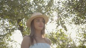 Cute young woman in straw hat and long white dress standing in the green summer garden. Sun shining behind the girl. Attractive young woman in straw hat and long stock video