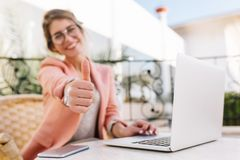 Cute young woman, student, business lady showing thumbs up, well done, sitting in outdoor cafe on terrace with laptop royalty free stock image