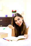 Cute young woman studying in bed at home Stock Photography