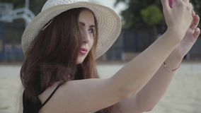 Cute young woman in the summer white hat taking selfie on her cellphone resting on the beach. Summer leisure concept. Portrait of young woman in the summer white stock video footage