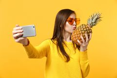 Cute young woman in sunglasses hold, kissing pineapple fruit doing selfie shot on mobile phone isolated on yellow orange royalty free stock images