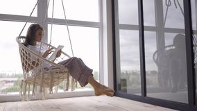 Cute young woman swinging in a hanging chair while using her tablet at the large floor-to-ceiling window. Freelance stock footage