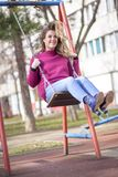 Reliving childhood, swinging in a park Royalty Free Stock Photo