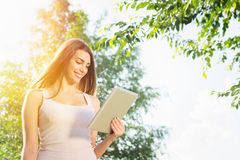 Cute young woman with tablet in park on sunny summer day Stock Images