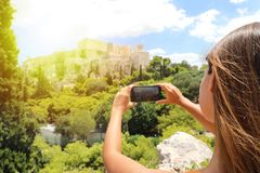 Cute young woman takes a picture of the Acropolis, Athens, Greece. Famous ancient Greek Acropolis is the main landmarks of Athens. Female tourist visits the royalty free stock image